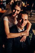 Portrait of the newlyweds in hard sunlight indoor