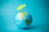 Global warming and climate change on earth concept. Earth globe on a blue background with an umbrella. Protecting the atmosphere from ultraviolet radiation and ozone holes