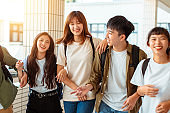 Group of happy students walking along the corridor at college