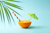 Food summer minimal concept. Orange juice and juicy tropical fruits on a light colored background