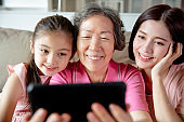 happy grandmother and daughter with granddaughter using phone taking selfie