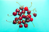 Cherry minimal background. Red summer cherry berries on a blue empty blue background. Summer fruits and food concept.