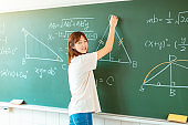 female student in the classroom writing on chalkboard  mathematical equations