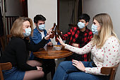 Four friends wearing face masks toasting with beer bottles in a pub