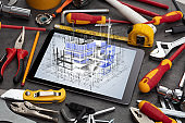 Tablet and tools with 3d house plan concept