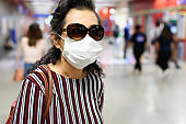 Old woman wearing a face mask and sunglasses