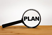 Focused on business concept. Magnifier glass with word plan on wooden table. Business concept. Search idea