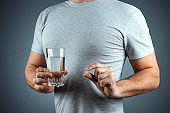 Male hands close-up, holds a glass of water and a pill, medication, treatment, gray background. Medical theme, vitamins, health care.