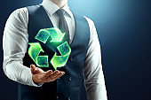 The businessman has a hologram of the recycling icon in the palm of his hand. Environmental pollution concept, plastic recycling, nature purification. Mixed environment.