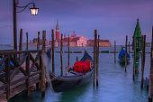 Venetian gondolas in San Marco pier and San Giorgio Maggiore at dusk, Venice, Italy