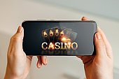 In the hands of a smartphone with playing cards the inscription casino, black-gold background. Concept of online gambling, online casino. Copy space.
