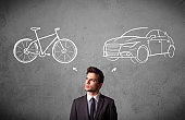 Businessman making a choice between bicycle and car