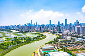 Drone view of rural green fields with fish ponds on Hong Kong and the skylines of Shenzhen