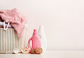 Laundry basket with towels, detergents, soap and bamboo balls on white background