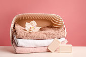 Stack of bath towels with white orchid flower in laundry basket and soap on pink background