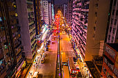 Car, taxi, and bus traffic on road intersection at night in Hong Kong downtown district, drone aerial top view. Street commuter, Asia city life, or public transportation concept