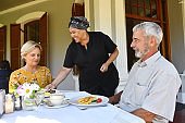 Female waitress serving breakfast to senior couple on an outdoor porch