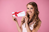 Portrait of beautiful woman giving a gift voucher