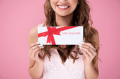 Close up of beautiful woman giving a gift voucher