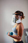 Side View Muscular young woman bicep curls with face shield and industrial face mask