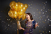Woman with balloons and champagne among confetti