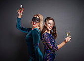 Portrait of women with masks and champagne at the party
