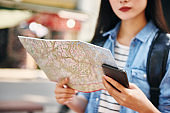 Close up of tourist with map and mobile phone