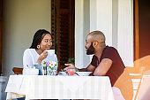 Couple on a restaurant veranda having a meal gossiping