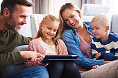 Cheerful family with tablet in living room