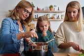 Three generations of women preparing food in the kitchen