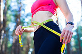 Photo of a fit and healthy young lady measuring her waist with a tape measure controlling her weight loss while training in the forest