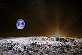 Sunrise above the moon surface. Blue Earth in the space. Moon is astronomical body that orbits planet Earth, being Earth's only permanent natural satellite. Elements of this image furnished by NASA.