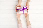Girls hands holding lovely present box