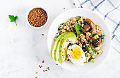 Breakfast oatmeal porridge with green herbs of mushrooms, boiled egg, avocado and flax seeds. Healthy balanced food. Top view, overhead,  copy space