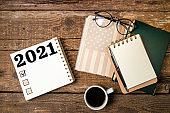 New year resolutions 2021 list. Office desk table with notebooks, coffee cup, american flag. Goal, plan, ideas, business, motivation, checklist