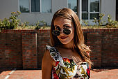 Smiling fashionable woman with sunglasses on a sunny day