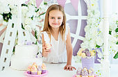 Pretty little blond girl standing in the beautiful decorated candy bar