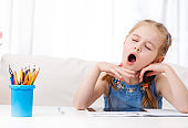 Little girl yawning at the table