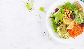 Vegetarian salad Buddha bowl dish with chickpea, avocado,  cucumber, carrot, chia seeds,  lettuce salad and olives. Healthy eating trend, superfood. Top view, flat lay, copy space