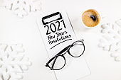 New year goals 2021 on desk. 2021 goals list with notebook, coffee cup and eyeglasses on white table. Resolutions, plan, goals, action, idea concept. New Year 2021 template