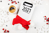 New year goals 2021 on desk. 2021 resolutions list with notebook, coffee on white desk. Goals, plan, resolutions, strategy, change, idea concept. Copy space