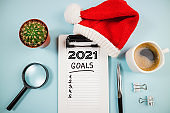 Top view 2021 goals list with notebook and coffee cup on blue desk. 2021 resolutions, goal, plan, strategy, business, idea