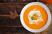 Pumpkin soup on rustic wooden table. Seasonal autumn food - Spicy pumpkin and carrot soup. Top view, flat lay, copy space