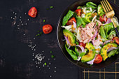 Tuna fish salad with lettuce, cherry tomatoes, avocado and red onions. Healthy food. French cuisine. Top view, copy space, flat lay