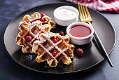 Traditional belgian waffles with berries, sour cream and jam on dark table.