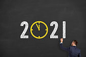 Business Person Drawing New Year Concepts 2021 Countdown Clock on Chalkboard Background