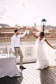 Interracial wedding couple. Destination fine-art wedding in Florence, Italy. African-American bride and Caucasian groom are dancing near the table for a wedding dinner, on the roof of the restaurant.