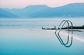 Reflection of the evening sky in the smooth water of the pool near the sea, against the backdrop of the mountains.
