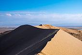 Sand dunes with clouds backgorund. Natural landscape. Altyn-Emel singing dunes or barkhan. Altyn-emel national park in Kazakhstan. Tourism travel in Kazakhstan concept.