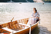 A wedding couple is sitting in a wooden boat on the Lago di Braies in Italy. Newlyweds in Europe, on Braies lake, in the Dolomites. The groom hugs the bride.